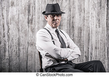 Hidden threat. Bossy senior man in gangster clothing sitting at the chair and looking at camera with a grey wall in the background