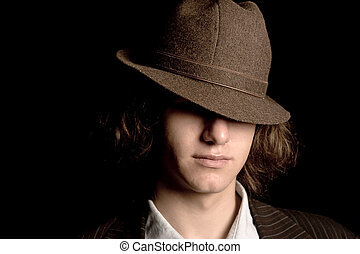 Hidding feature - Male teenager with a hat tipped over the...