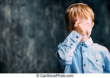 hide and seek - Five year old boy covered his eyes with his...