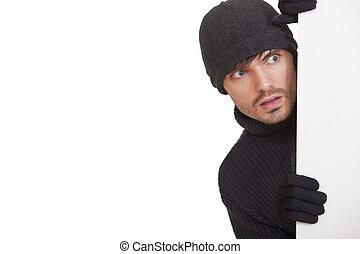 hiding burglar - burglar in black hat hiding under white...