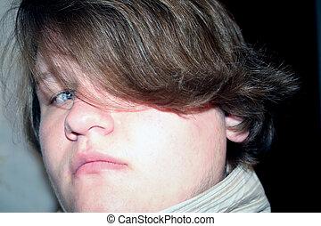 Hiding - Closeup of teenage boy with hair over one eye.