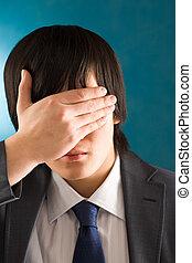 Hiding face - Portrait of young businessman hiding his face...