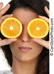 Hiding her eyes with oranges