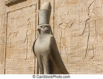Hieroglyphic carvings on an ancient egyptian temple wall with statue