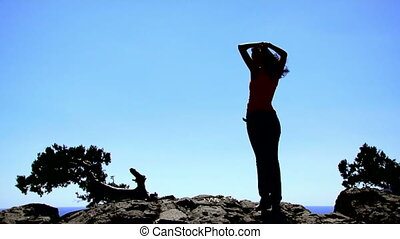 High above the sea - Beautiful girl standing on a high cliff...