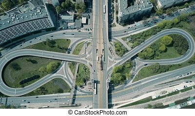 High altitude aerial shot of big urban road junction on a sunny day, top down view. 4K video