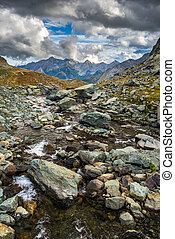 High altitude alpine stream with dramatic sky - High...