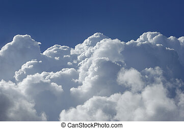 Cumulus clouds shot from a high altitude against a blue sky