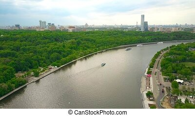 High altitude panoramic aerial shot of Moscow river tour boats and city skyline as seen from Vorobievy Gory. 4K video