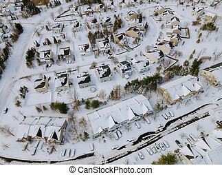 High altitude view of city with snow covered roofs houses neighborhood town residential