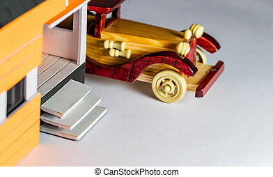 High angle close up shot of a vintage toy car parked behind a house made with craft materials.