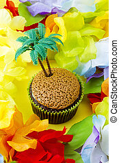High angle close-up shot of cupcake with plastic coconut tree miniature surrounded by colorful flowers.