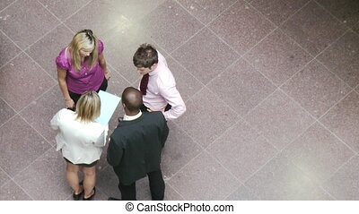 High angle of business people shaking hands in building -...