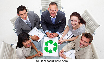 High angle of business team looking at a recycling symbol. ...