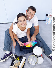 High angle of couple chosing colours to paint new house - ...