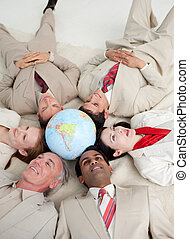 High angle of International business people lying on the floor around a terrestrial globe