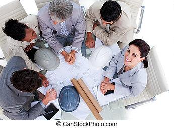 High angle of multi-ethnic architects studying blueprints