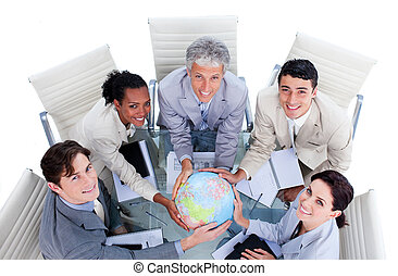 High angle of positive business people holding a terrestrial globe in a meeting