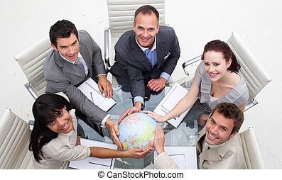 High angle of smiling business team holding the world. ...