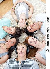 High angle of teenagers listening to music - High angle of...