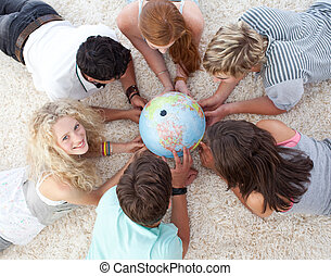 High angle of teenagers lying on the floor examining a terrestrial world