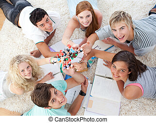 High angle of teenagers studying Science on the floor
