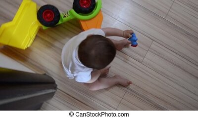 High Angle rotating shot, cute seven months old baby boy playing with educational toys on the floor