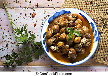 spanish caracoles en salsa, cooked snails in sauce