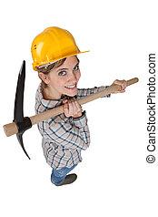 High-angle shot of a tradeswoman carrying a pickaxe