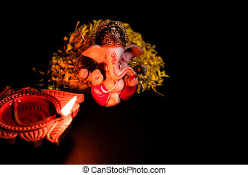 high angle shot of beautiful ganesha statue with clay lamp glowing against black background. faith concept.