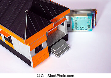 High angle shot of money bundles behind a house model made with craft materials.
