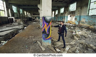 High angle shot of young urban artist decorating high column...