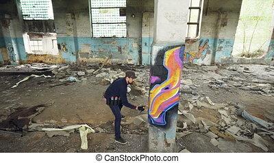 High angle shot of young urban painter creating abstract...