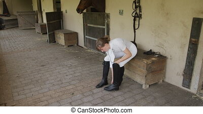 High angle side view of a beautiful young Caucasian woman putting on her boots before horse riding, in slow motion