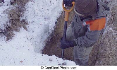 Ecologist in the forest digging a soil slit - High angle...