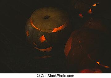view Illuminated jack o lanterns in darkroom - High angle ...