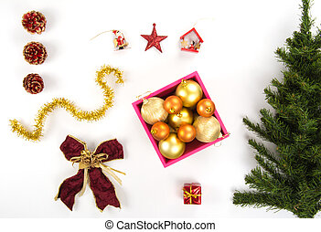 High angle view of a collection of Christmas ornaments and a plastic pine tree on a white background