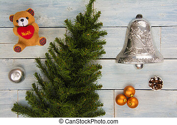High angle view of a collection of Christmas ornaments and a plastic pine tree on a wooden background
