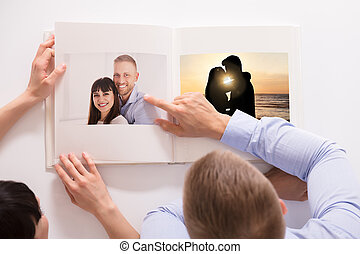 High Angle View Of A Couple Looking At Their Photo Album