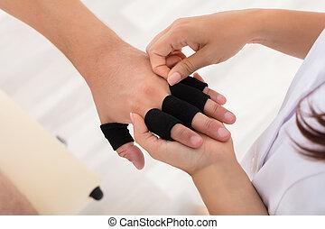 Doctor Putting Finger Protector Sleeve On Man's Finger