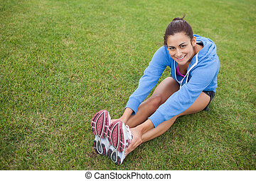 High angle view of a pretty sporty woman stretching her legs while sitting on the grass