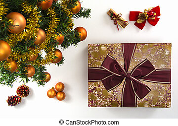 High angle view of a wrapped gift, a collection of Christmas ornaments and a plastic pine tree on a white background