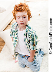 High angle view of adorable little boy with hands in pockets kneeling on carpet and looking away