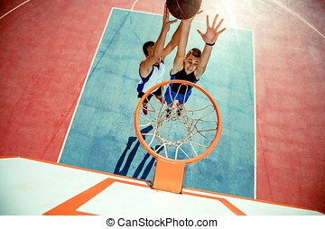 High angle view of basketball player dunking basketball in...