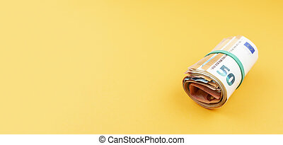 big money roll of euro banknotes with rubber band against orange background