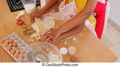 High angle view of black mother and daughter rolling dough in kitchen of comfortable home 4k