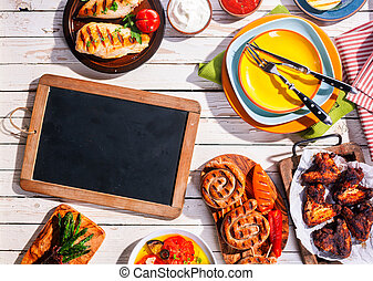 Blank Chalkboard on Picnic Table with Grilled Meal