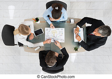 Businesspeople Discussing Start-up Plan - High Angle View Of...