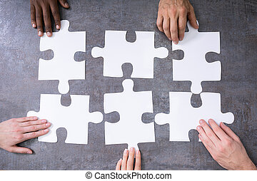 High Angle View Of Businesspeople Solving Jigsaw Puzzle