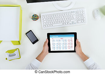 Businessperson With Digital Tablet Showing Calendar